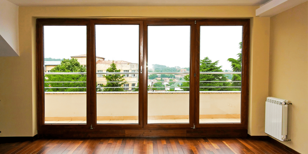 large windows on a wall with a wide view of trees and houses
