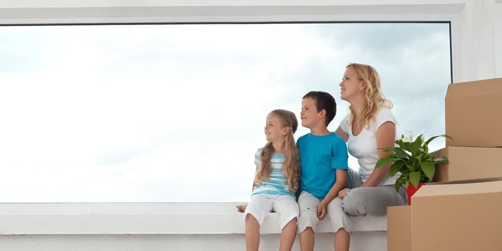 mother and her son and daughter are siting in front of an energy saving window